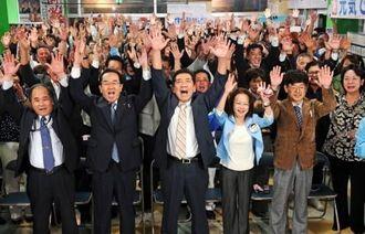 バンザイ三唱で当選を祝う桑江朝千夫氏(前列中央)ら=27日午後10時23分、沖縄市中央の選対事務所