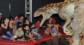 会場を動き回る肉食恐竜ラプトルに驚く親子連れ=19日、豊見城市・豊崎ライフスタイルセンターTOMITON(松田興平撮影)