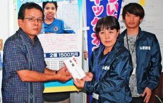 共同代表の當山みゆきさんに寄付金を手渡す仲村毅専務(左)=8日、北谷町