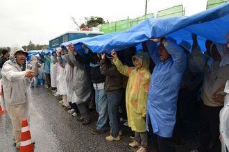 雨の中、工事車両の進入を警戒する人たち=2日、名護市辺野古の米軍キャンプ・シュワブゲート前