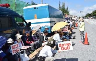 工事用車両が米軍キャンプ・シュワブ内に入るのを、座り込んで警戒する市民ら=7日午前9時30分ごろ、名護市辺野古の国道329号沿い