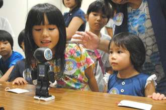 声を掛けると動くロボットに興味津々の子どもたち=10日午前、那覇市・沖縄タイムス社