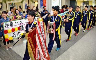 9年ぶり5度目の優勝を飾り、保護者らの歓迎を受ける男子興南=那覇空港