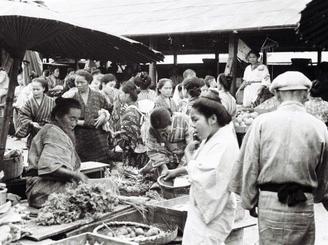 戦前に現在の那覇市東町にあった「那覇ウフマチ(大市)」と呼ばれた市場。出店者がお金を支払い、一定のスペースを借りて、商売が行われた。建物の中のほか、路上に商品を並べて露店販売をする人々もおり、庶民生活の場としてにぎわった。写真は、野菜などの農作物を販売している場所と見られ、女性たちが野外で「バーキ」と呼ばれる竹かごに品物を入れて対面販売をしている。(写真は朝日新聞社提供)