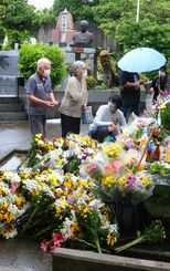 たくさんの花や飲み物が供えられた魂魄の塔。断続的に雨が降る中、遺族らは戦没者の冥福を祈って手を合わせたり、じっと塔を見つめたりしていた=23日午後1時55分ごろ、糸満市米須