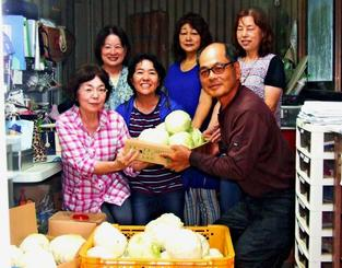仲村さん(前列左)にキャベツを手渡す瑞慶覧さん=14日、北中城村渡口合同会社Z農園