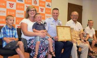 男児の救命活動に貢献した米軍嘉手納基地消防所属のロジャー・ハリーさん(中央)=19日、北谷町役場