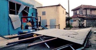 大型倉庫入り口の屋根部分が約15メートルにわたって崩れた。倉庫のトタンも一部がめくれ、内部が見えていた=祖納地区(金井瑠都通信員撮影)