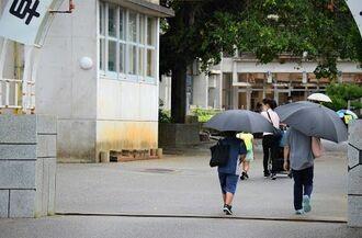 臨時休校が決まった沖縄県糸満市内の小学校。雨の中、登校する児童はまばらだった=7日午前、糸満市内