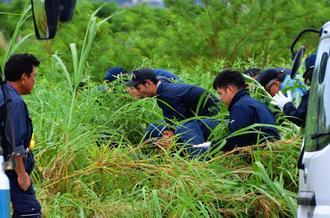 女性が殺害された現場付近を捜索する県警の捜査員=5月30日午後、うるま市内