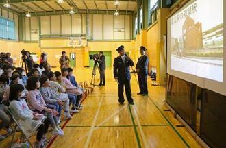 震災前のJR双葉駅の画像を見る小学生ら=20日午後、福島県いわき市