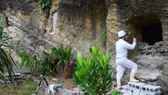 トゥダチを調査する沖縄国際大学の宮城弘樹講師。左奥は空墓で、真ん中は石で入り口が封鎖されている=22日、うるま市平安座島