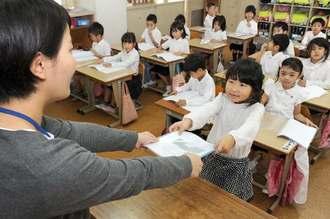 先生から「よいこのあゆみ」を受け取る児童=22日午前、糸満市・西崎小学校