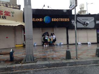 商店の軒先で雨風を避ける生徒=4日、那覇市国際通り