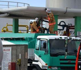 出火したタンクローリーを調べる消防士。屋根には火災の際に付いたとみられる黒いすすが確認できる=石垣市美崎町
