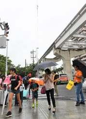 雨の中、傘を差して登校する児童ら=16日午前7時50分、那覇市牧志