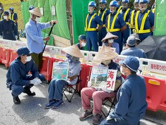 資材搬入のゲート前に座り込む市民と立ち退くよう求める機動隊員=6日午前9時過ぎ、名護市のキャンプ・シュワブゲート前
