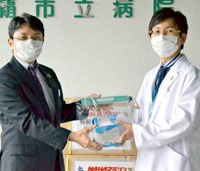 知念覚副会長(左)からマスクとフェースシールドを受け取る中田円仁副センター長=22日、那覇市立病院
