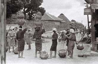 芋入りのバーキ(竹かご)を二段重ねにして頭に乗せた女性たちが集まる市場の風景。現在の糸満市糸満の町端区、通称「西新地ン門(にしみーじんじょー)」の街道側とみられる(朝日新聞社提供)