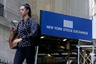 ニューヨーク証券取引所の入口を通りすぎる女性=16日(AP=共同)