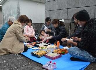 先祖に家族の健康を祈ったあと、持ち寄ったごちそうを食べる平良さんの親族=9日、宮古島市・袖山墓地公園