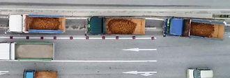 荷台の底が見えるほどの量の土砂を名護市安和の桟橋に搬入するダンプトラック=7月16日(沖縄ドローンプロジェクト提供)