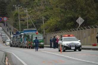 パトカーに先導され米軍キャンプ・シュワブゲートに向かう工事車両=3日、名護市辺野古