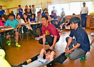 Tシャツとほうきを使った手作りの担架で搬送を体験する教員ら=8日、沖縄市・県立泡瀬特別支援学校