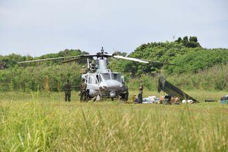 不時着した機体の周辺で作業する米軍関係者ら=6日午前9時40分すぎ、うるま市・津堅島