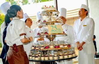 開業25周年を祝ってバースデーケーキの火を吹き消すロワジールホテル那覇のスタッフら=2日、同ホテル