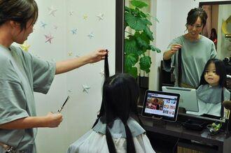 カットした髪を見つめる長浜妃桜等ちゃん(右)=27日、那覇市国場の美容室「quaint」