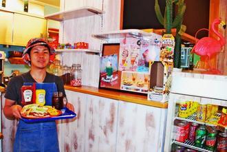 木目調のやわらかい雰囲気の店内で、サンドイッチを提供する又吉悟さん=那覇市安謝