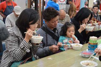 年越しそばを食べる家族=31日、那覇市の平和通り