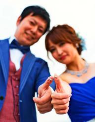 指の腹にイラストを描いてポーズを取る新郎新婦(ビック沖縄提供)