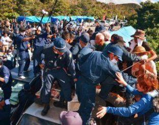 ヘリパッド建設に反対し、車の上で座り込む住民らを排除する機動隊=22日午前9時7分、東村高江のN1地区出入り口(下地広也撮影)
