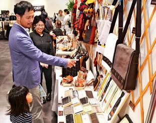 久米島紬を使ったカバンやネクタイを品定めする来場者=7日、那覇市久茂地・タイムスギャラリー