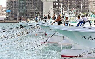 台風接近に備え、漁船をロープで固定する漁業関係者=20日午後2時、那覇市・泊漁港(田嶋正雄撮影)