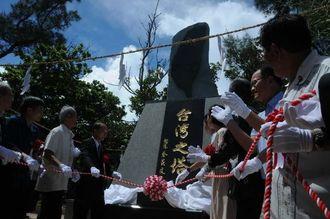 台湾之塔の除幕式でロープを引く関係者ら=25日、糸満市摩文仁・県平和祈念公園