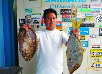 瀬良垣海岸で60センチ、2・24キロのタマンと46センチ、1・76キロのカーエーを釣った恵俊春さん=7日