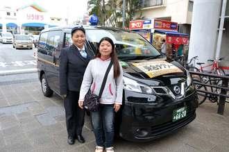 那覇市が実証実験する「乗合タクシー」を利用する外間幸枝さん(右)と乗務員の内嶺清美さん=ゆいレール安里駅前