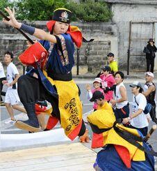 民家の庭先の特設ステージで棒術を披露。鮮やかな棒さばきにランナーも思わず拍手を送る=2009年、糸満市米須