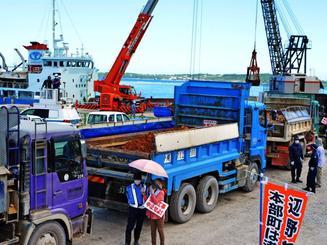 名護市辺野古の新基地建設現場へ資材を輸送する運搬船へ土砂を運び入れるダンプカー=25日、本部港塩川地区