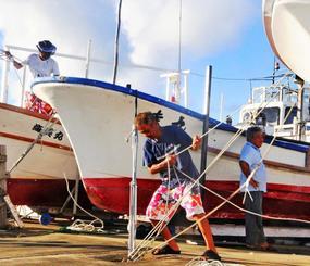 台風18号の接近で、陸揚げした船をロープで固定する漁業者=12日午前7時45分ごろ、石垣市新栄町・石垣漁港