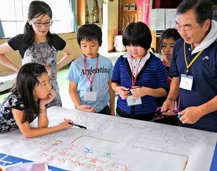 取材やフィールドワークを基に地図を作製する児童ら=17日、糸満市大里公民館