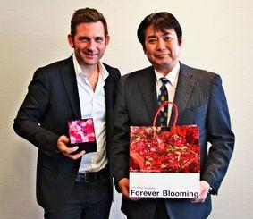 イベントへの来場を呼び掛けるニコライ・バーグマン氏(左)とリウボウインダストリーの花城正二店舗企画部長=4日、沖縄タイムス社
