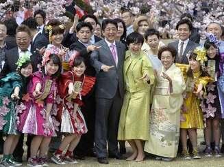 「桜を見る会」で招待客と記念写真に納まる安倍首相(中央左)と昭恵夫人(同右)=15日午前、東京・新宿御苑