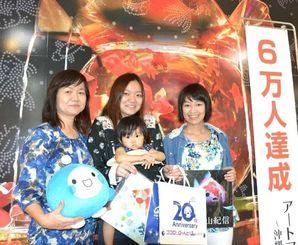 アートアクアリウム展入場者6万人目となった瀬良垣千恵子さん(左)の家族=25日、那覇市のデパートリウボウ