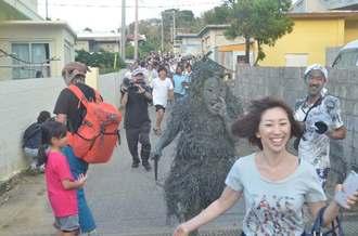 パーントゥに泥を塗られまいと、逃げる女性=8日夕、宮古島市平良島尻