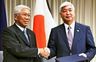防衛協力・交流に関する覚書に署名し握手する中谷防衛相(右)とフィリピンのガズミン国防相=29日午後、防衛省