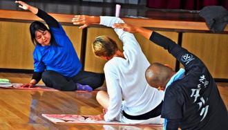 ヨーガ療法士の玉城志保さん(左)の指導のもと、瞑想や体操でリラックスする沖縄ダルクの利用者=宜野湾市内
